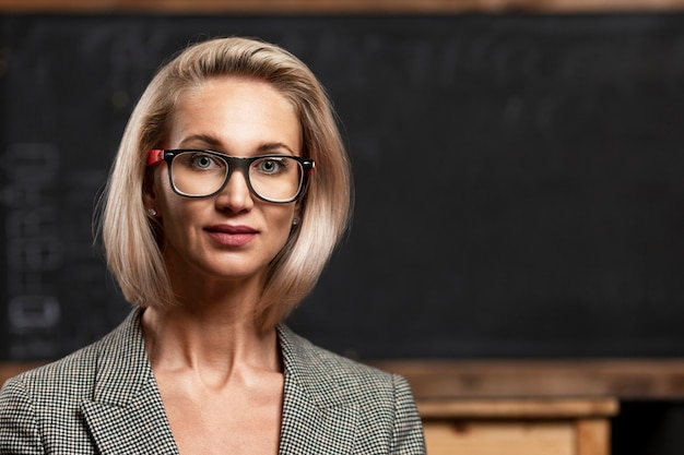 A young blonde woman teacher with glasses stands in a class near a black school board. distance learning. close-up. space for text.