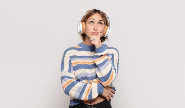 若いブロンドの女性は、さまざまなオプションで、疑わしくて混乱していると感じ、どの決定を下すのか疑問に思っています