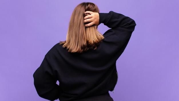 Молодая блондинка думает или сомневается, почесывает голову, чувствует озадаченность и замешательство, вид сзади или сзади
