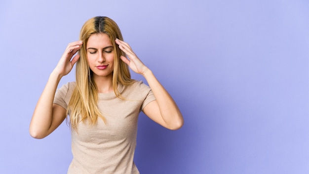 こめかみに触れて頭痛を持っている若いブロンドの女性
