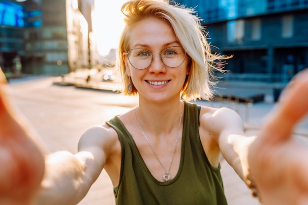 Young blonde woman tourist wearing glasses makes selfie on the background of modern glass buildings in the city center.
