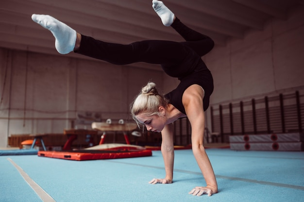 Молодая блондинка тренируется для чемпионата по гимнастике