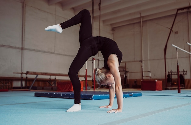 体操オリンピックのための若いブロンドの女性のトレーニング