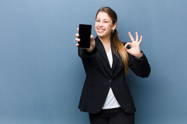 Молодая белокурая женщина используя smartphone против стены grunge