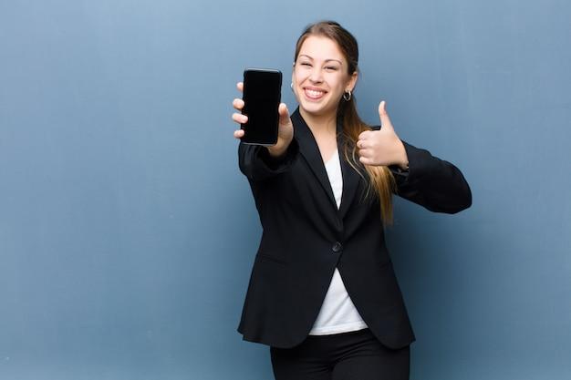Молодая блондинка с помощью смартфона на стене гранж