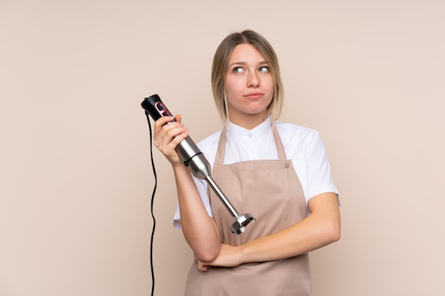 Young blonde woman using hand blender making doubts gesture while lifting the shoulders