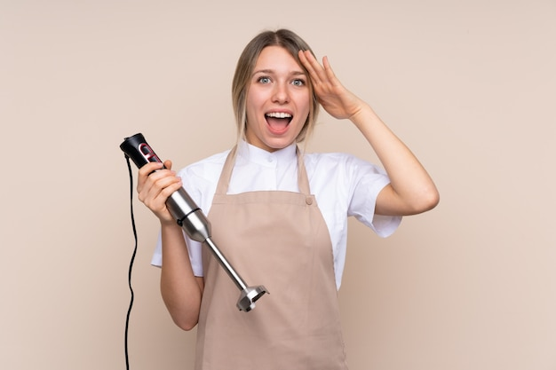 Young blonde woman using hand blender with surprise and shocked facial expression