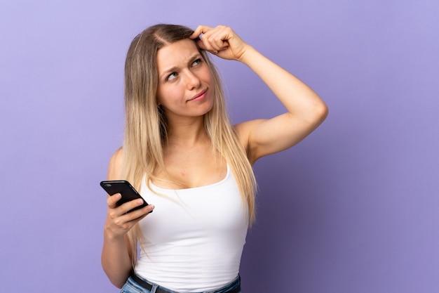 疑念と混乱した表情で紫色の壁に隔離された携帯電話を使用して若い金髪の女性