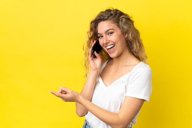 横に指を指している黄色の背景に分離された携帯電話を使用して若いブロンドの女性