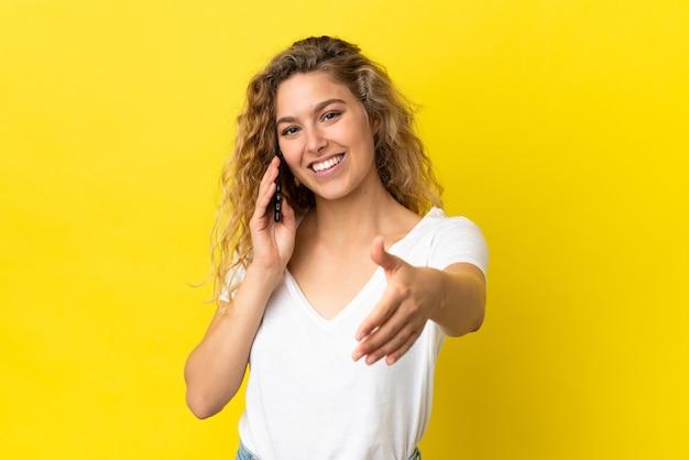 Молодая блондинка женщина с помощью мобильного телефона изолирована на желтом фоне, пожимая руку для закрытия хорошей сделки
