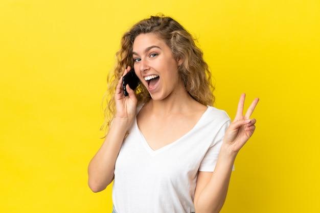 Молодая блондинка женщина с помощью мобильного телефона изолирована на желтом фоне улыбается и показывает знак победы