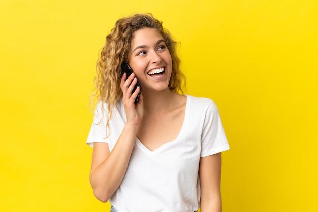 노란색 배경에 격리된 휴대전화를 사용하는 젊은 금발 여성이 올려다보는 동안 아이디어를 생각하고 있다