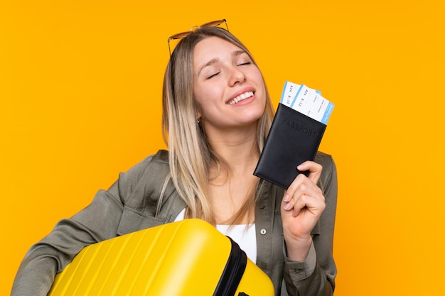 Young blonde woman in vacation with suitcase and passport