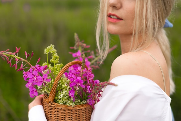 若いブロンドの女性は、野生のピンクの花のバスケットを持って田舎を歩きます