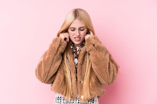 手で耳を覆うピンクの壁にコートを着ている若いブロンドの女性。