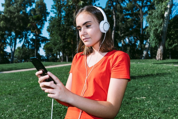Молодая блондинка в красной рубашке смотрит на мобильный и слушает музыку в парке