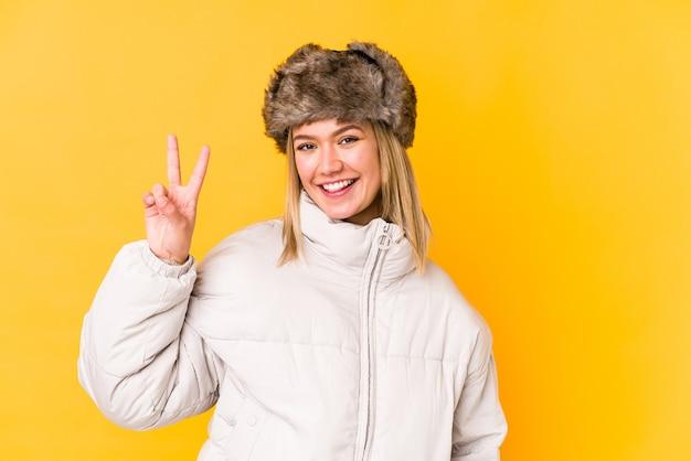 隔離された冬の服を着ている若いブロンドの女性黄色の壁に隔離された若いブロンドの女性は、勝利のサインを示し、広く笑っています。