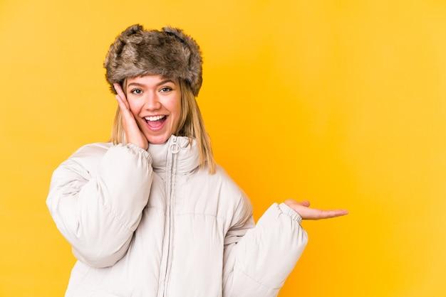 孤立した冬の服を着ている若いブロンドの女性