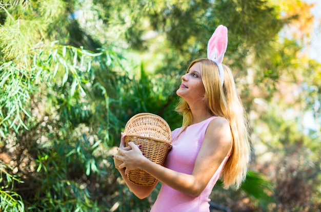 Young blonde woman wearing bunny ears and with colorful easter eggs