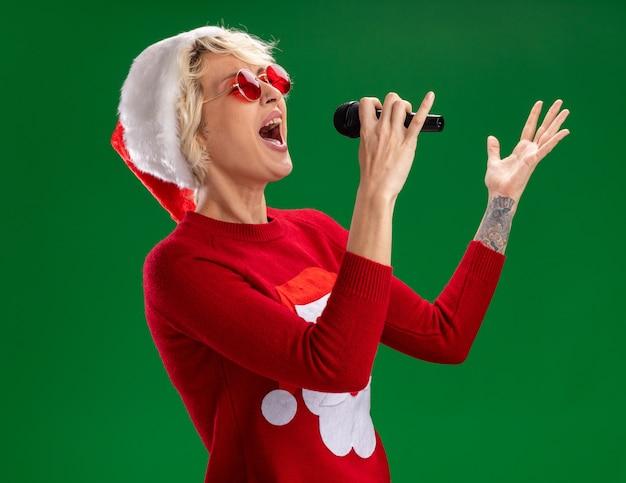 クリスマスの帽子とサンタ クロース クリスマス セーターを着た若い金髪の女性のプロファイル ビューに立って、緑の壁に目を閉じて歌う空気に手をつないでいるマイクを持って立っています。