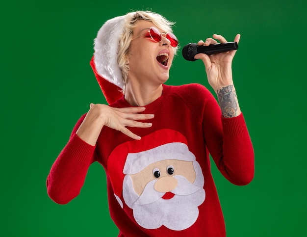Young blonde woman wearing christmas hat and santa claus christmas sweater with glasses holding microphone near mouth touching chest singing with closed eyes isolated on green background