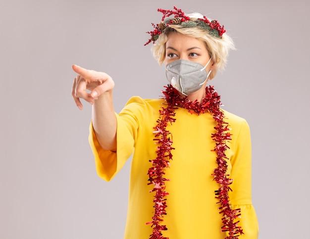 Giovane donna bionda che indossa la testa di natale ghirlanda e tinsel ghirlanda intorno al collo con maschera protettiva guardando e rivolto verso il lato isolato su sfondo bianco