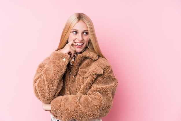 Young blonde woman wearing a coat against a pink background relaxed thinking about something looking at a copy space.