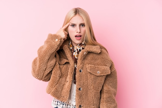 Young blonde woman wearing a coat against a pink background showing a disappointment gesture with forefinger.