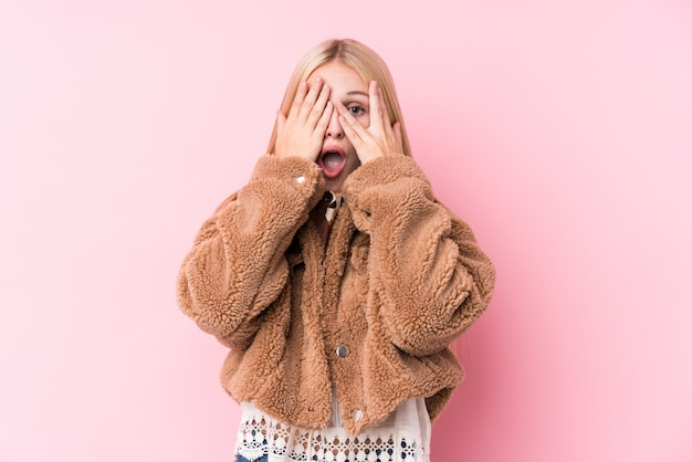 Young blonde woman wearing a coat against a pink wall blink through fingers frightened and nervous.