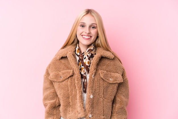 Young blonde woman wearing a coat against a pink wall happy, smiling and cheerful.