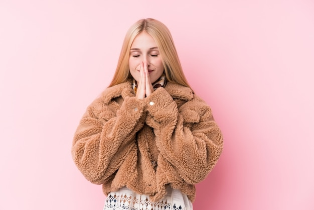 Young blonde woman wearing a coat against a pink wall holding hands in pray near mouth, feels confident.