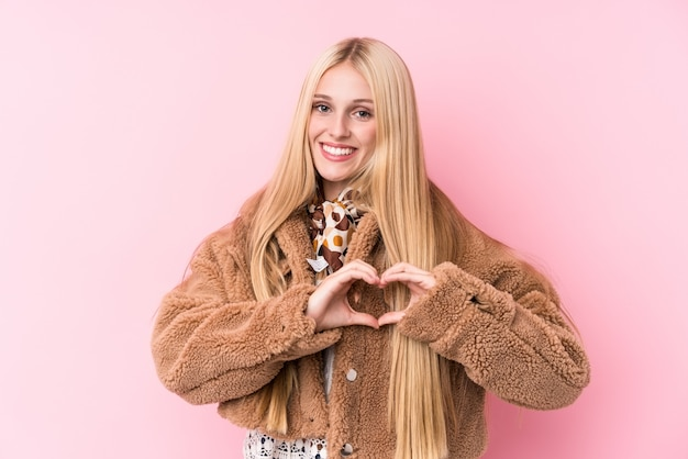Young blonde woman wearing a coat against a pink wall smiling and showing a heart shape with hands.