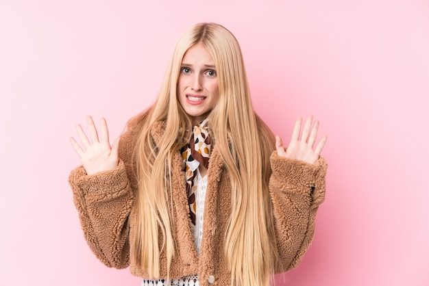 Young blonde woman wearing a coat against pink