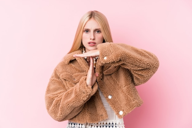 Young blonde woman wearing a coat showing a timeout gesture