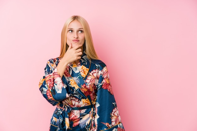 Young blonde woman wearing a kimono pajama looking sideways with doubtful and skeptical expression.