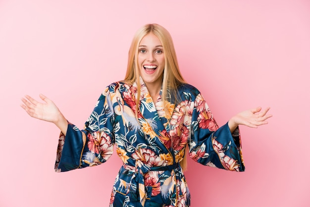 Young blonde woman wearing a kimono pajama receiving a pleasant surprise, excited and raising hands.