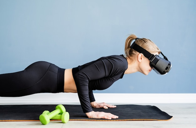 Young blonde woman wearing virtual reality glasses doing push ups at home