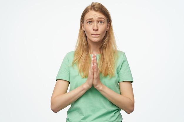 若いブロンドの女性は、緑のtシャツを着て、彼女の手を祈りの位置に保ち、良い試験結果を祈る