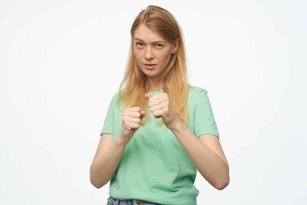 若いブロンドの女性は、ボクシングのスタンスで立って、女性の権利のために戦う準備ができて、緑のtシャツを着ています