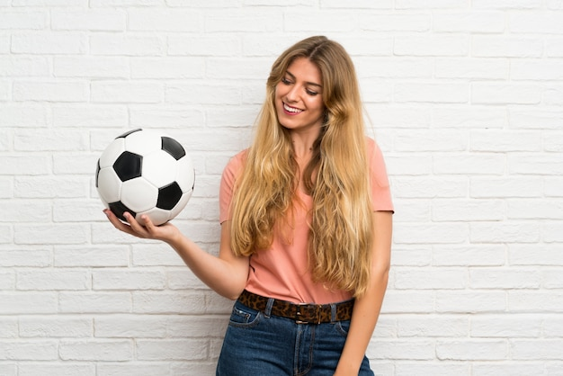 Young blonde woman over white brick wall holding a soccer ball