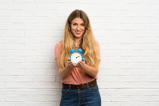 Young blonde woman over white brick wall holding vintage alarm clock