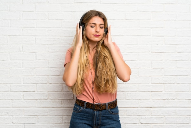Young blonde woman over white brick wall listening to music with headphones