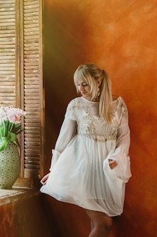 Young blonde woman in white dress dancing by the window romantic love happiness concept