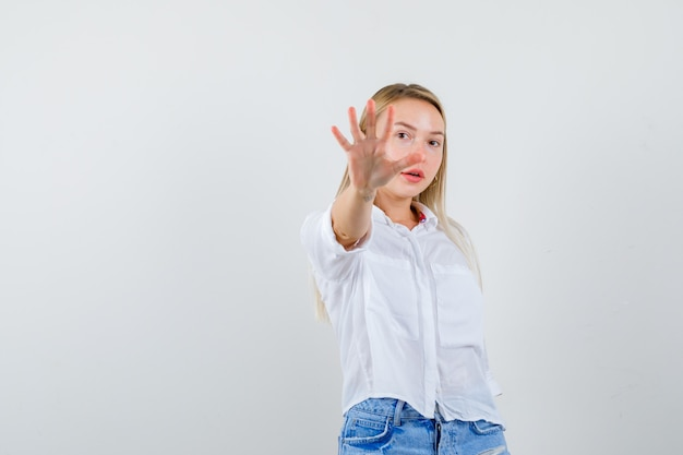 Giovane donna bionda in camicia bianca