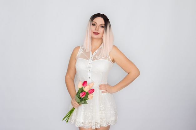 Young blonde woman in white spring dress holding bouquet of pink tulips in her hands. mothers day concept. womens day. 8 march