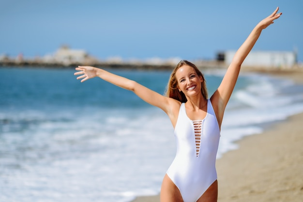 Young blonde woman in white swimsuit on a tropical beach with open arms.