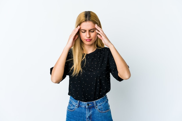Young blonde woman on white wall touching temples and having headache.
