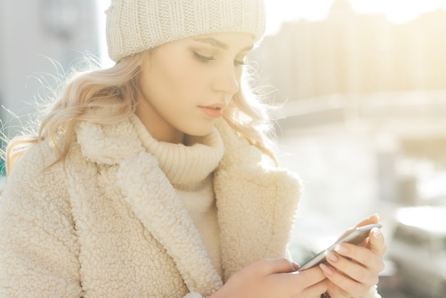 Young blonde woman in winter clothes looks into the smartphone and smiling.