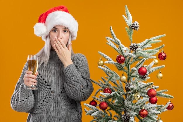 Giovane donna bionda in maglione grigio invernale e cappello da babbo natale con in mano un bicchiere di champagne scioccata c