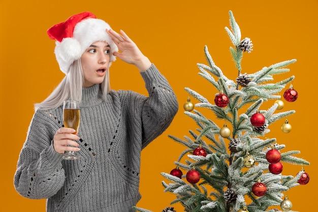 Giovane donna bionda in maglione grigio invernale e cappello da babbo natale con in mano un bicchiere di champagne guardando lontano con la mano sopra la testa in piedi accanto a un albero di natale sul muro arancione